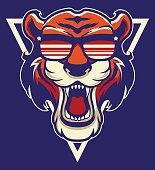 Cool Tiger Mascot. Strong Wildlife Animal Head Isolated On Blue Background. Angry Mammal In Hipster Glasses Sticker, Logo, Patch, Emblem. Wild Cat Color Old School Tattoo, Apparel Print Design