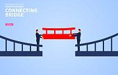 Cooperation, two businessmen connect the bridge