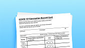 istock Coronavirus vaccination record card on blue background with copy space for travel and movement without borders. Vaccination form during the coronavirus covid 19 epidemic 1312253694