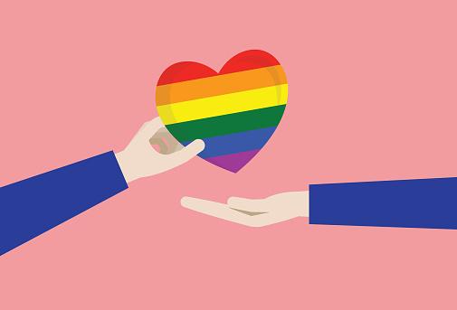 A couple gives a rainbow heart