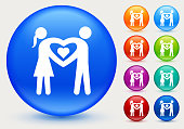 Couple in love icon. The icon is white and is placed on a round blue vector button. The button has a sight shadow and the background is light. The composition is simple and elegant. The vector icon is the most prominent part if this illustration. There are eight alternate button variations on the right side of the image. The alternate colors are orange, red, purple, maroon, light blue, green, teal and indigo.