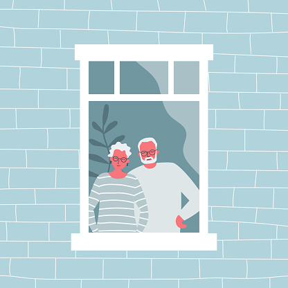 Couple of elderly people are standing at the open window. An old woman and an old man are looking out the window from their apartment