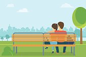 Couple outdoors in the park sitting on bench and looking