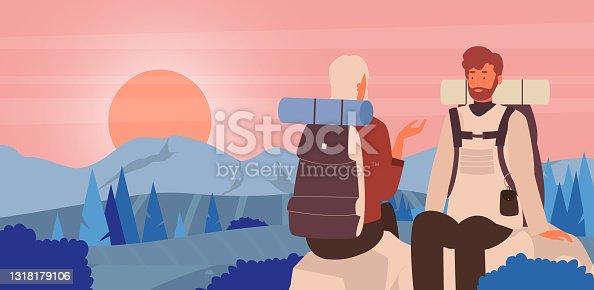 istock Couple people enjoy sunset scene in mountain landscape, hiker tourists sitting on stones 1318179106