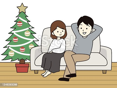 istock Couple sitting on the couch for Christmas. 1346093098