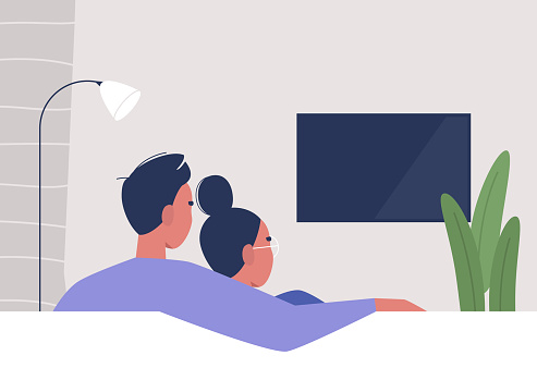 A couple watching TV at home, weekend relaxation, modern lifestyle