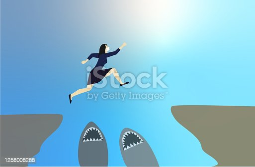 istock Courageous and motivated woman jumps. Business concept idea. 1258008288