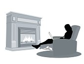 A vector silhouette illustration of a young woman using her lap top reclining in a chair in front of a fireplace.