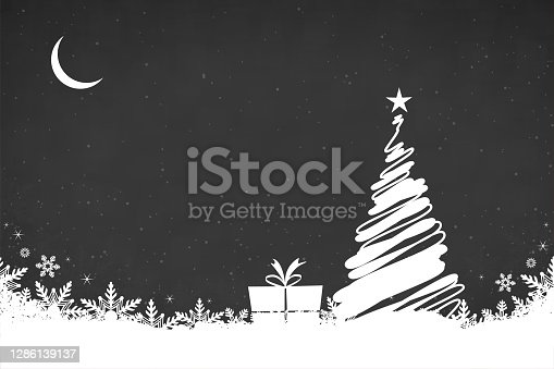 istock Creative dark black coloured backgrounds with one white scribbled christmas tree with a bright shining star at top, a present and snowflakes all over the ground and crescent moon in the sky 1286139137