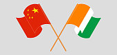Crossed and waving flags of China and Republic of Ivory Coast. Vector illustration