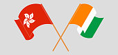 Crossed and waving flags of Hong Kong and Republic of Ivory Coast. Vector illustration