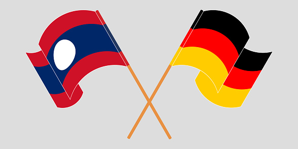 Crossed and waving flags of Laos and Germany