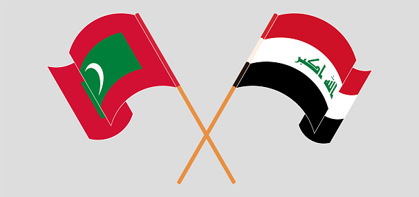 Crossed and waving flags of Maldives and Iraq