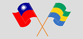 Crossed and waving flags of Taiwan and Gabon. Vector illustration