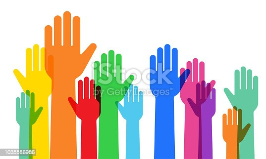 A crowd raising hands