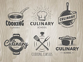 Culinary school logos. Vector labels for cooking classes, workshops and courses. Set of monochrome badges with chefs hat, pans and kitchenware on vintage wooden background