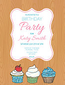 Birthday party invitation with cupcakes on wood background