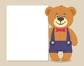 Cute brown Teddy bear holds a white sheet of paper for text.