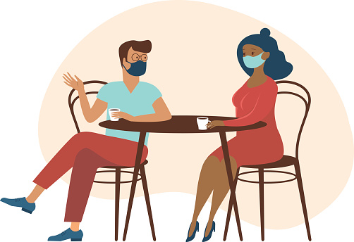 Cute couple wearing protective medical maskssitting at table, drinking tea or coffee and talking. New cafe visiting regulations during coronavirus COVID-19 outbreak.