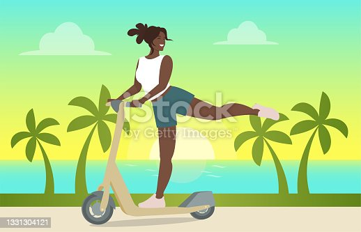 istock A cute dark-haired girl in a yellow dress rides a scooter, lifting her leg and smiling 1331304121