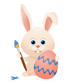 Cute easter bunny, rabbit painting an easter egg isolated vector