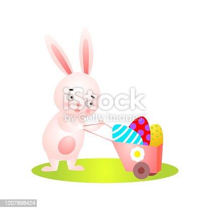istock Cute easter rabbit on green grass full wheelbarrow 1207898424