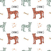 istock Cute funny safary seamless vector pattern with cheetahs, bones and roar quotes. Infantile style nursery Art with leopard cats perfect for Fabric, Textile. Hand drawn modern illustration in nice colors 1304017046