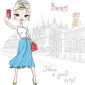 Cute hipster girl makes selfie in Bruges, Belgium