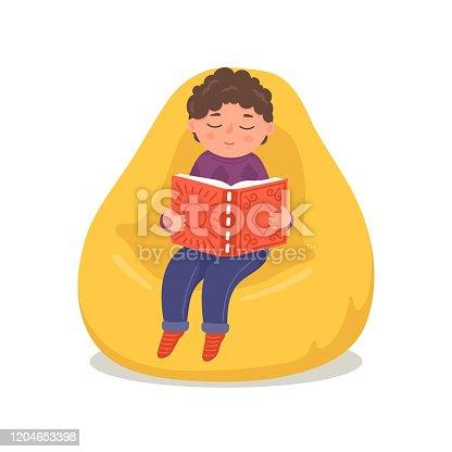 Cute little boy reading book in bean bag