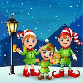 Cute little kid elves with snowfall falling