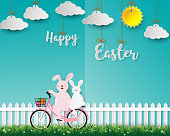 Cute rabbits on bicycle happy in the garden for Easter holiday,celebrate party,invitation or greeting card