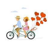 cute romantic cheerful couple riding tandem bike with heart shaped balloons