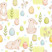 A cute seamless pattern with rabbits, carrots and colored eggs. Easter spring design with buns. Imitation of handmade watercolors. Cartoon flat vector illustration. Isolated on a white background.