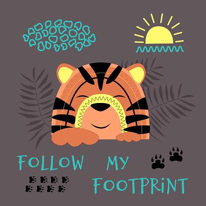 Cute tiger cub follows the tracks.
