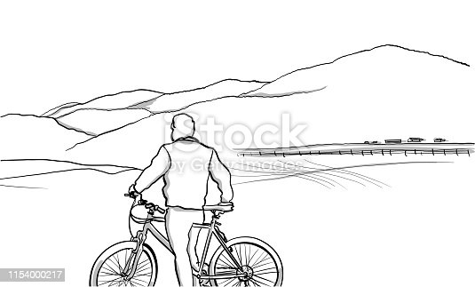 Cycling tourist taking a pause to look at the landscape in the countryside