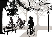 A vector silhouette illustration of cyclists riding along a path in a park.  Two parents and a child ride along part of an intersection while a young lady rides past a bench.