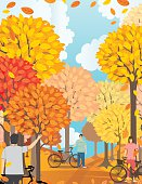 Cycling Tourism Concept. People are riding bicycles though a wilderness area. It is fall and they are surrounded by orange and yellow leaves.