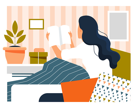 Daily life concept. Young woman sitting at home reading a book