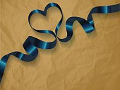Dark blue ribbon on a crumpled paper brown background.