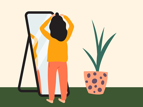 Dark-haired girl doing half up top knot in front of a mirror. Woman wearing comfy clothes at home getting ready to go out. Flat vector illustration