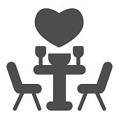 istock Date at a restaurant solid icon, valentine day concept, set table with chairs and heart sign on white background, romantic evening icon in glyph style for mobile concept. Vector graphics. 1287527290