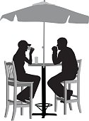 A vector silhouette illustration of a young man and woman having drinks outside on a patio under and umbrella.