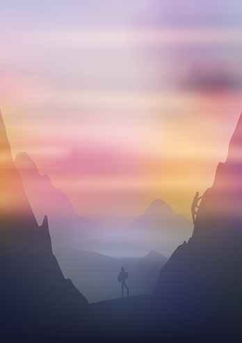 Dawn above mountains, climbers on the cliffside