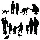 A Set of Silhouetts showing a family holding hands & feeding animals at the park.