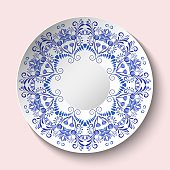 Decorative plate with blue floral ornament in a circle. Empty space in the center. The ethnic style of painting on porcelain. Vector illustration.