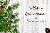 Decorative Spruce branches with pine cones and snow on a white wooden background, Christmas theme illustration.