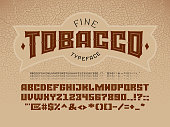 Decorative vintage font on the background of the texture of the tobacco leaf