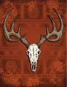 A beast of a deer skull rests on a grungy Southwestern style rug background.