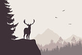 Deer with stags standing at the top of rock with mountains and forest in the background, under the sky with flying birds