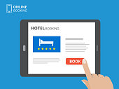 Design concept of hotel booking online. Tablet computer with hand touching a screen. Display with book button and bed icons. Mobile application for renting accommodations.